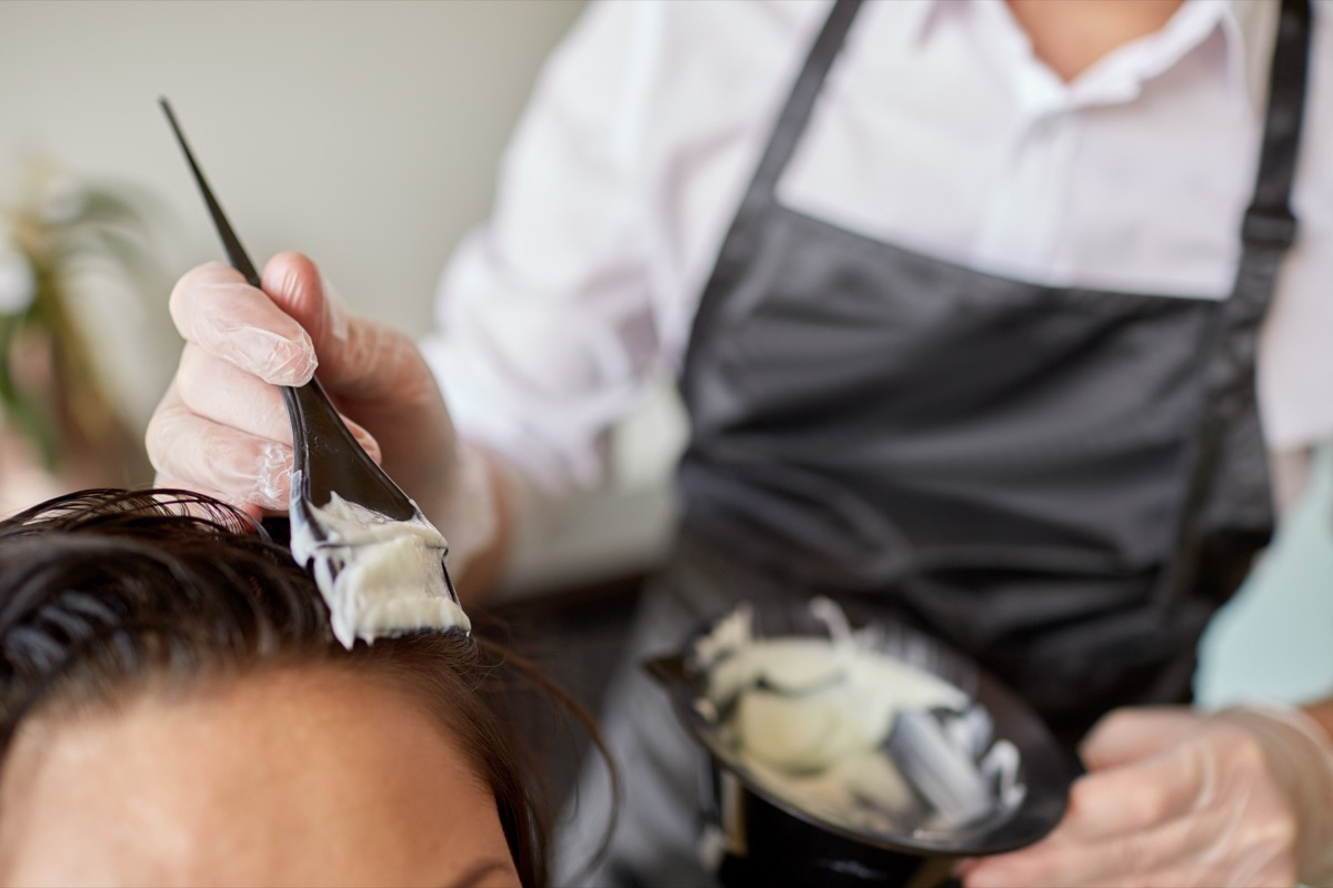 beauty and people concept - close up of stylist with hair dye and brush coloring hair at salon - Image