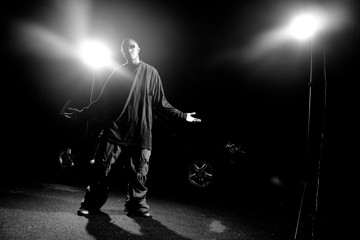 African American young man wearing baggy clothing posing under dramatic lighting with lens flare. - Image