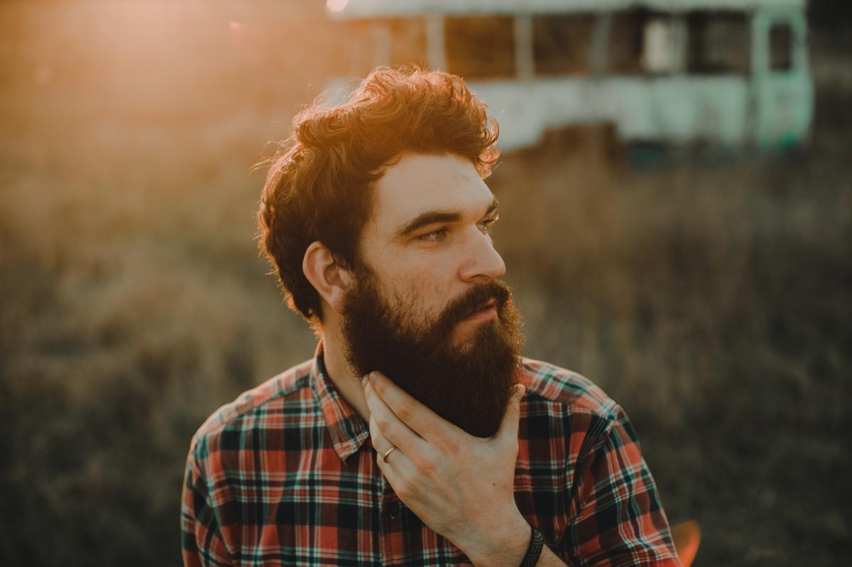 hipster man stroking his beard