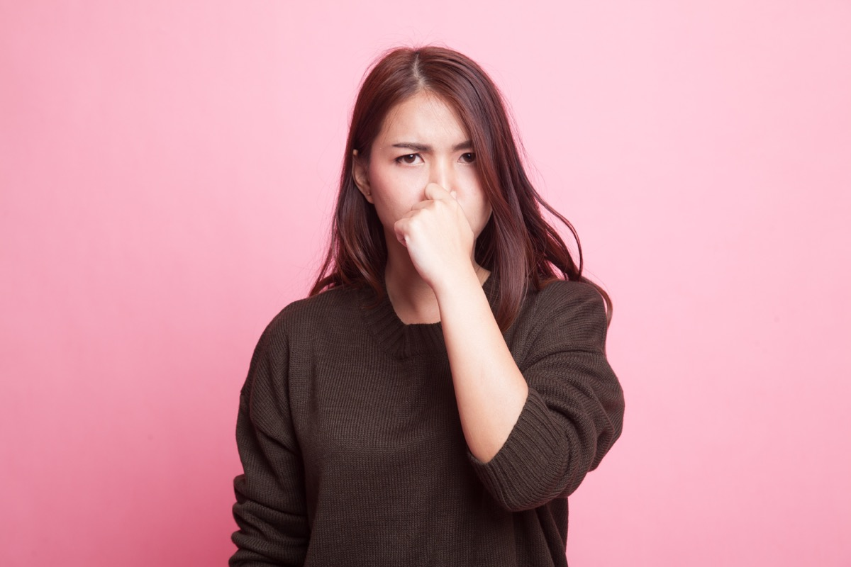 Young Asian woman holding her nose because of a bad smell on pink background - Image