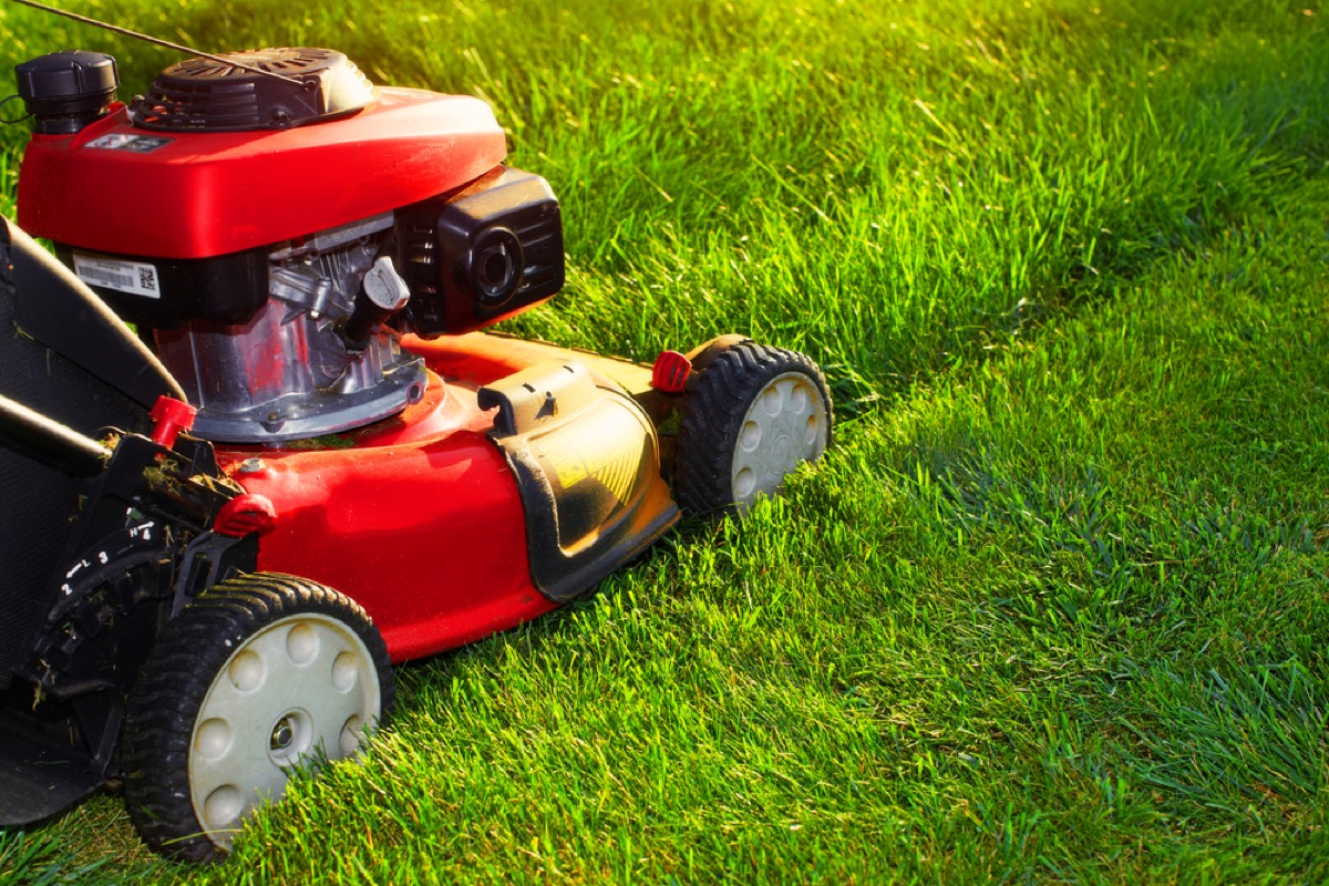 person mowing lawn with electric lawnmower, fire prevention tips