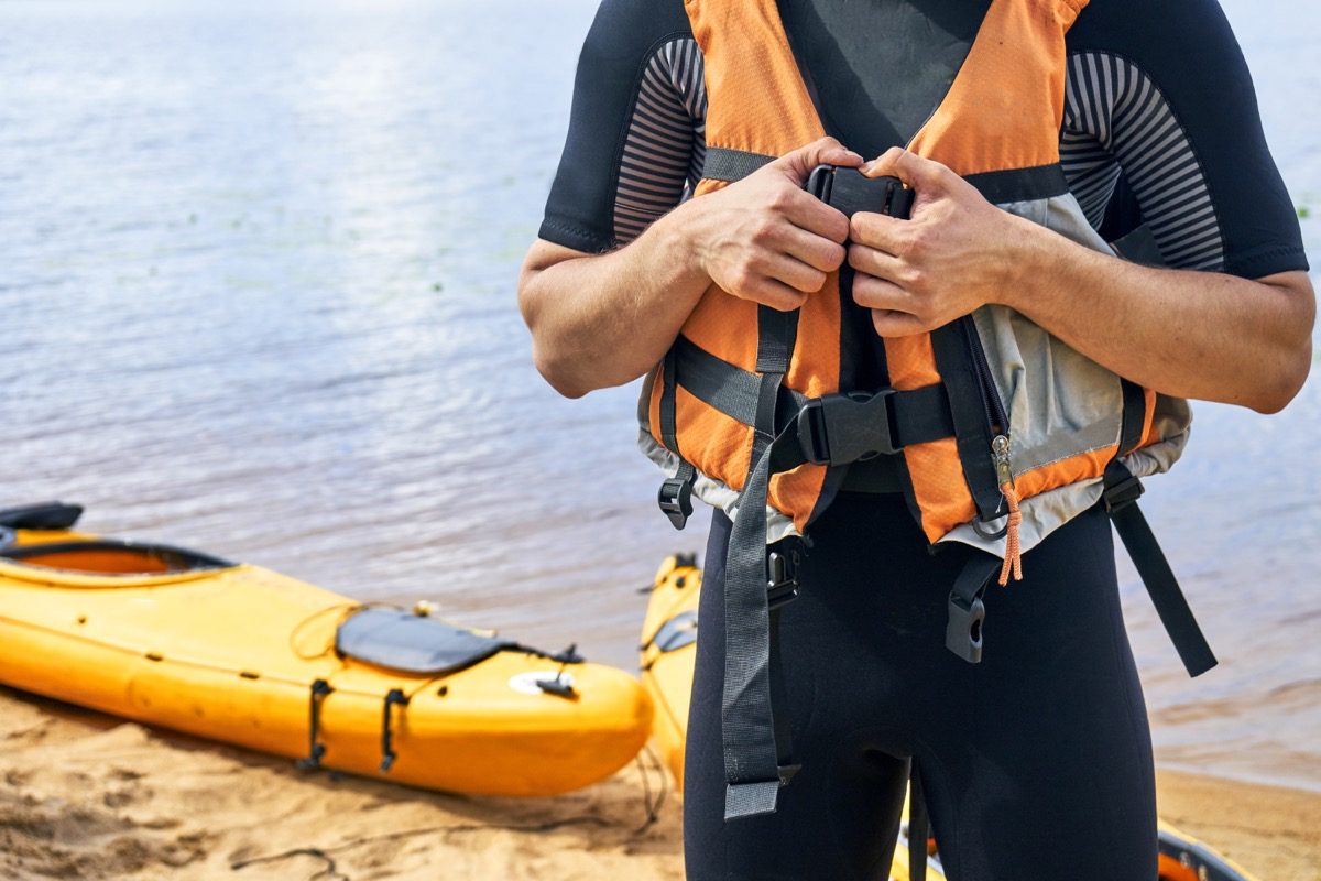 man connecting his life jacket together in front of a lake