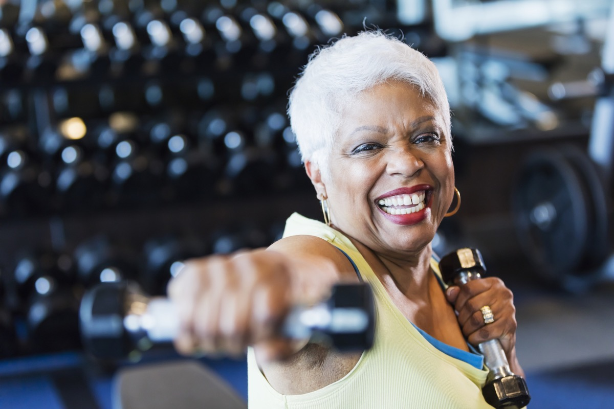 Older woman lifting weights at the gym