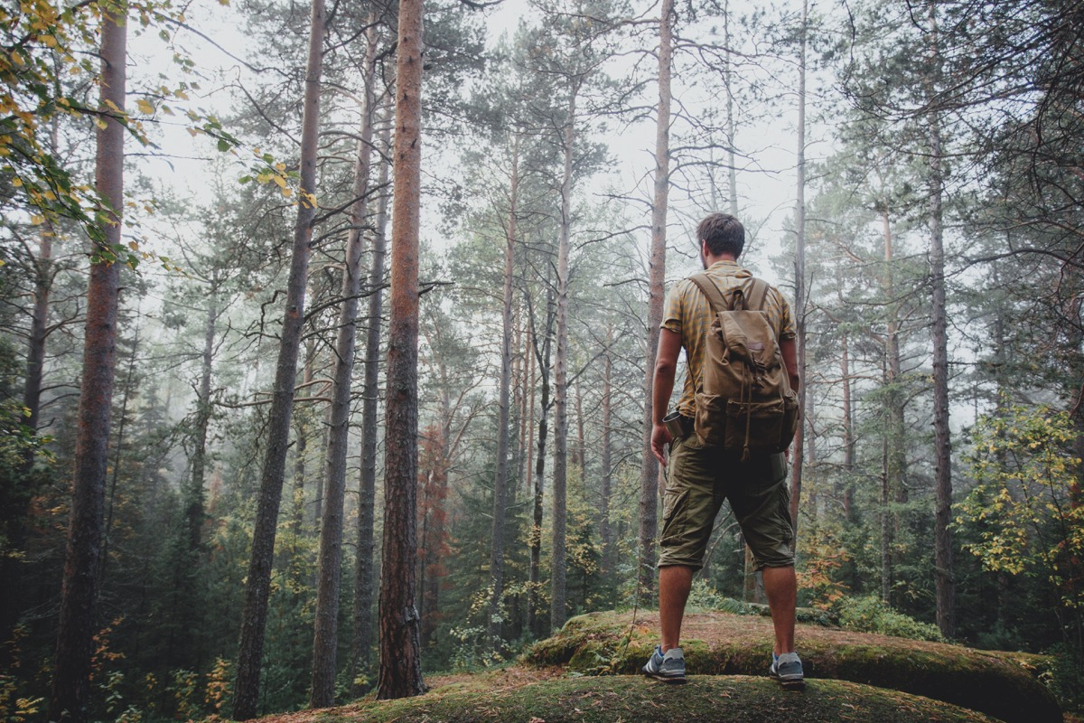 man backpacking through the woods alone