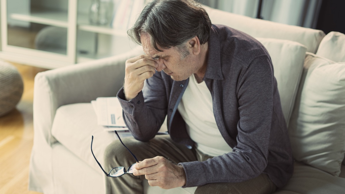 Man sitting on the couch holding his temples feeling stressed