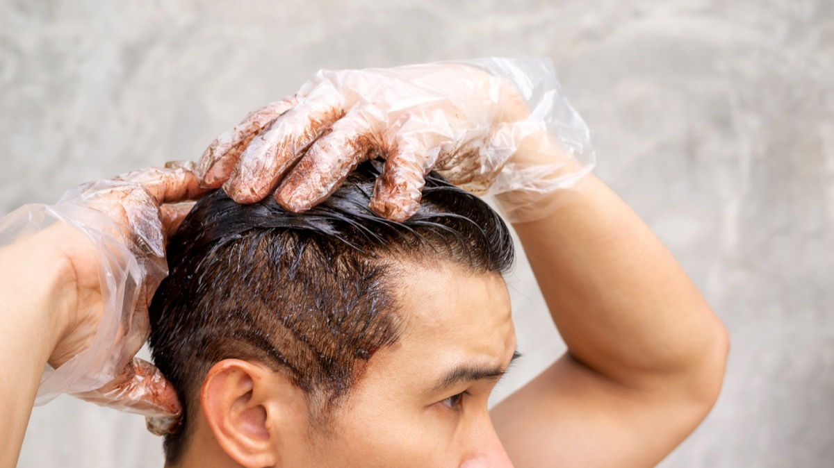 Asian men dye his hair color on a gray background. - Image