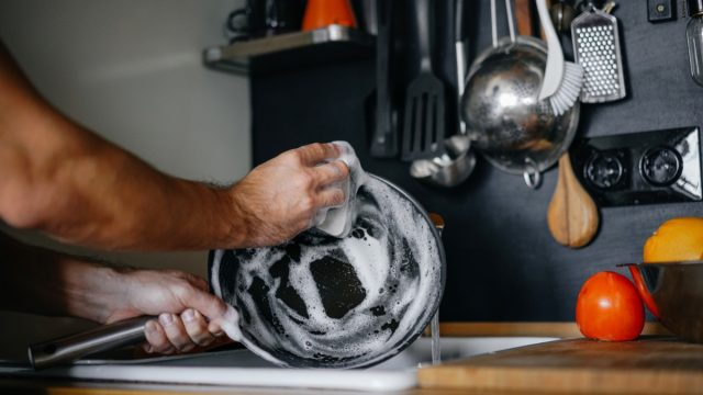 man hand-washing a cast iron pan, new uses for cleaning products