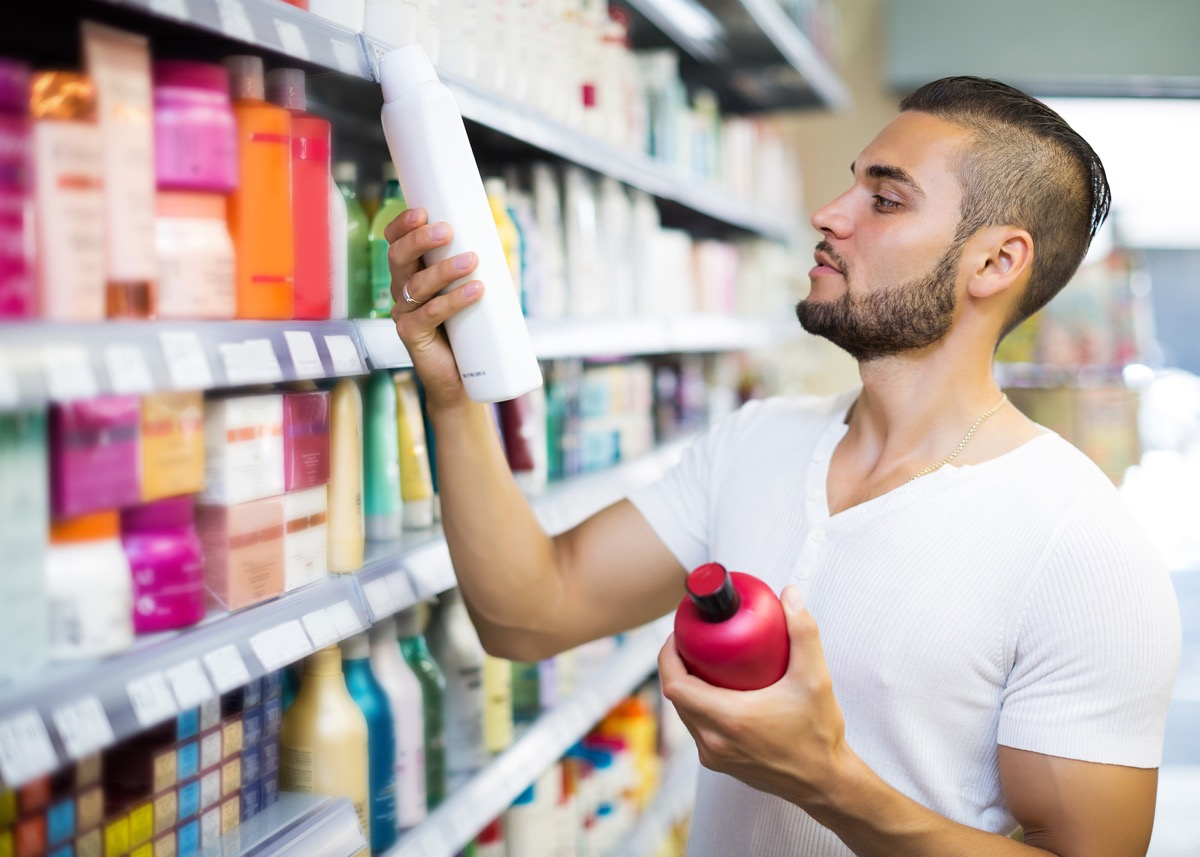 Attractive man buying shampoo in shopping mall - Image