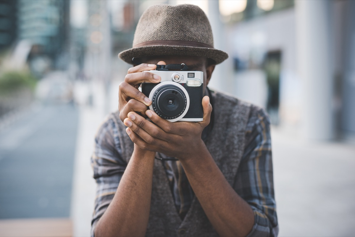 Half length of young beautiful afro black man outdoor in the city holding instant camera, shooting - photography, creative, artist concept - Image