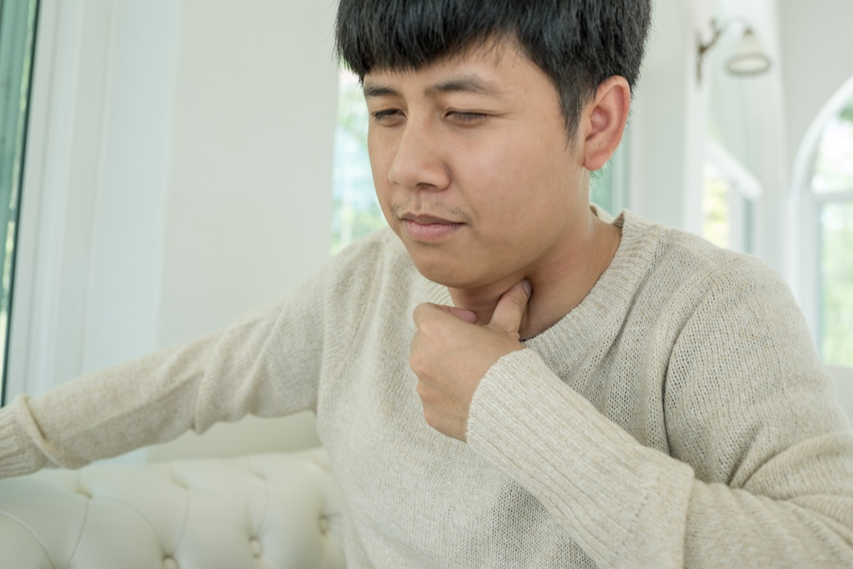 Asian man holding his throat in pain