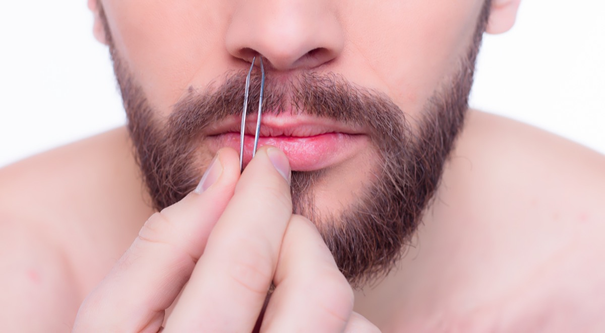 Young handsome bearded man in front of a mirror with tweezers in his hands. - Image