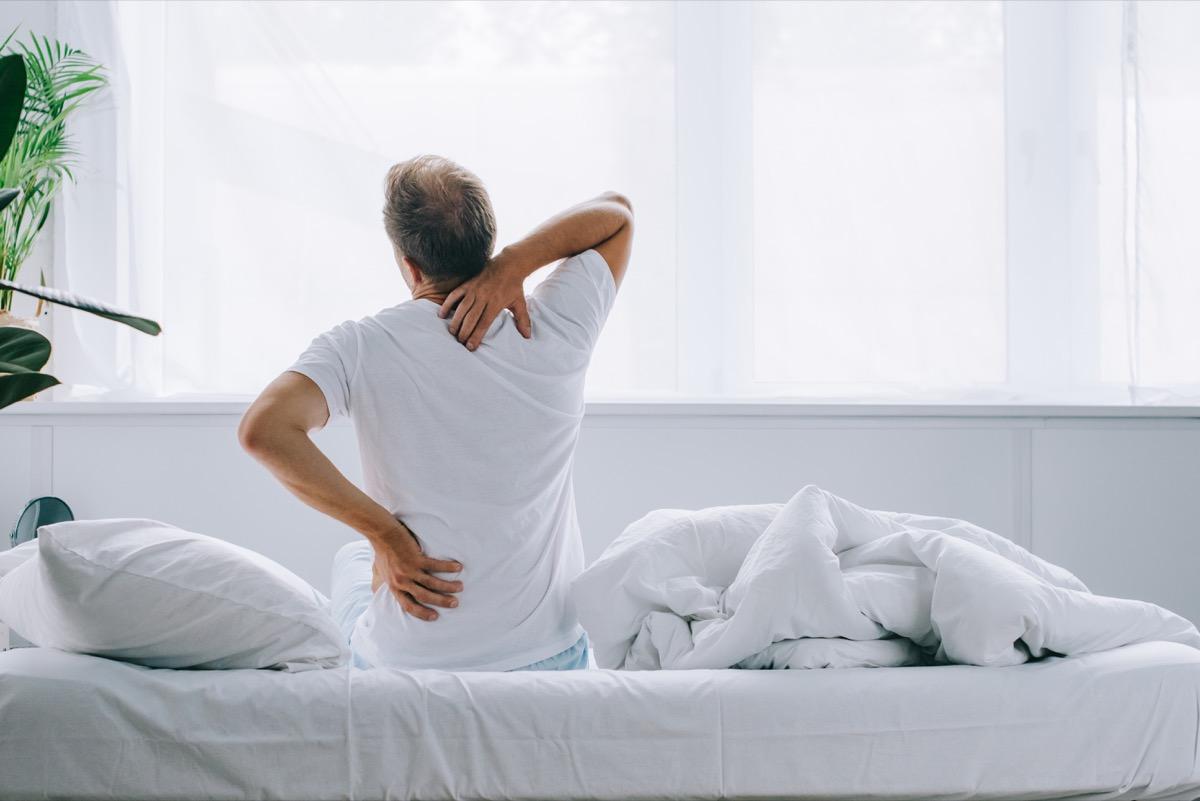 man with back pain sitting on a bed