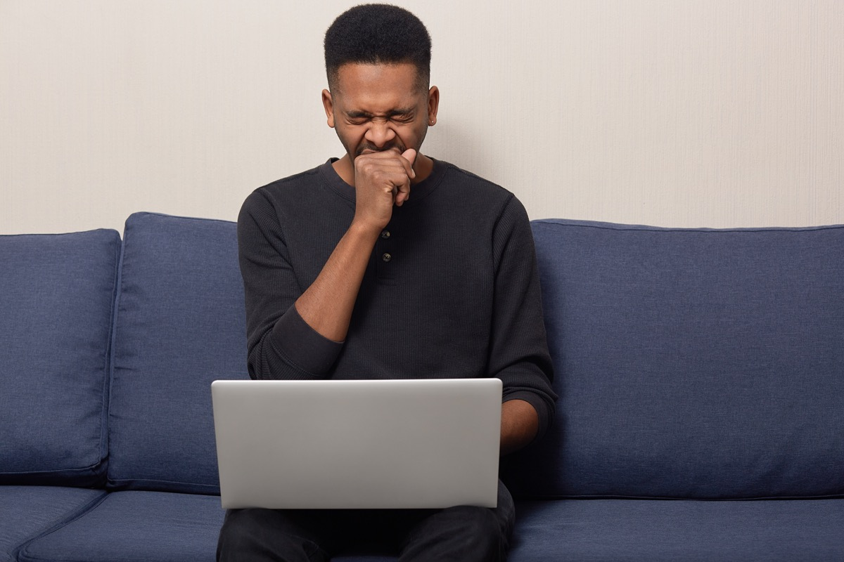 Man Yawning While He Scrolls on His Laptop, contagious conditions