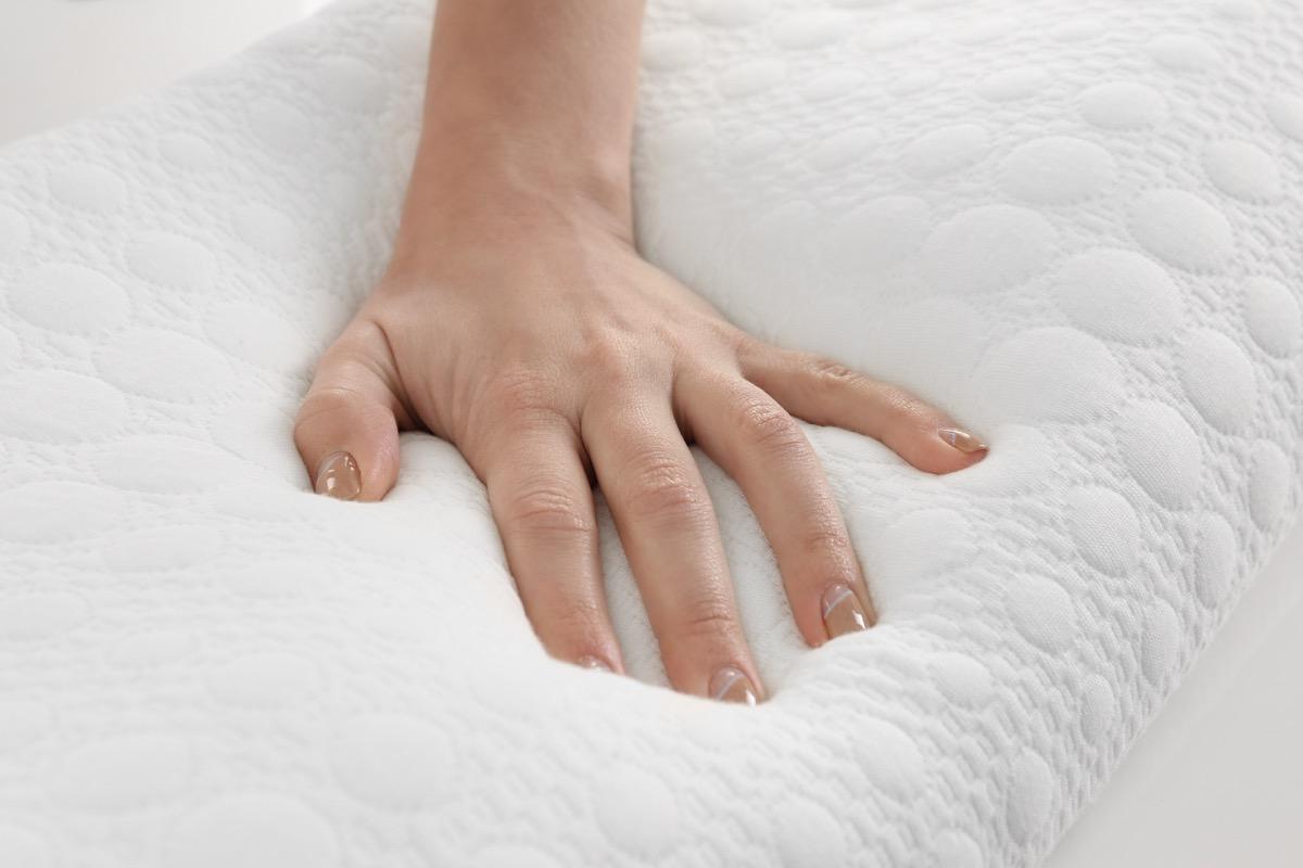 white hand on memory foam pillow