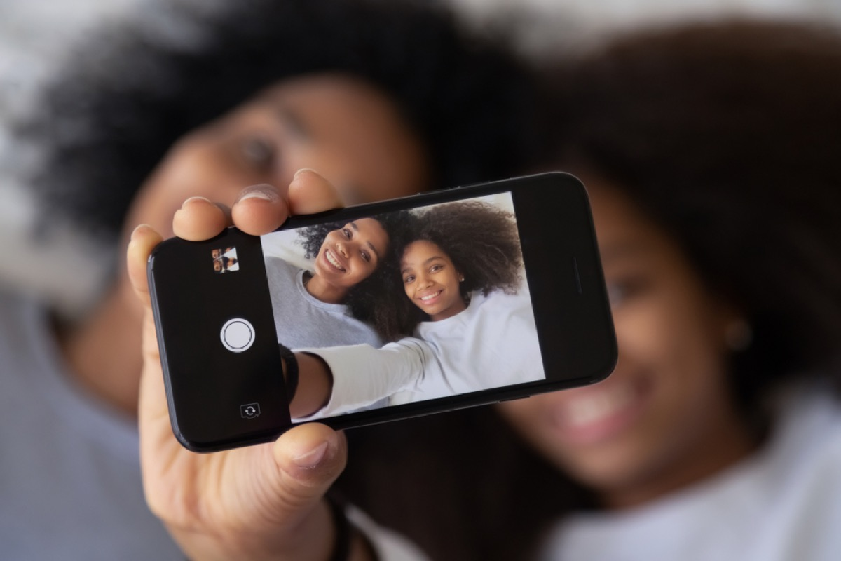 mom and daughter taking photo of themselves on phone, parenting is harder
