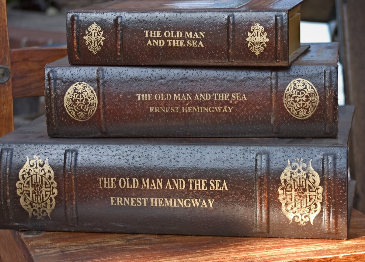 Three stacked leather bound books by Ernest Hemingway. - Image
