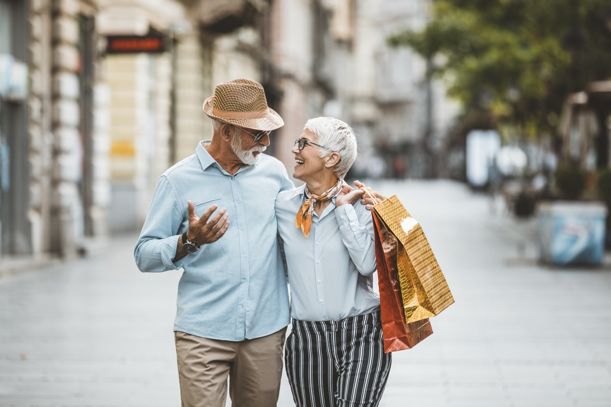 older couple walking together with shopping bags after going shopping