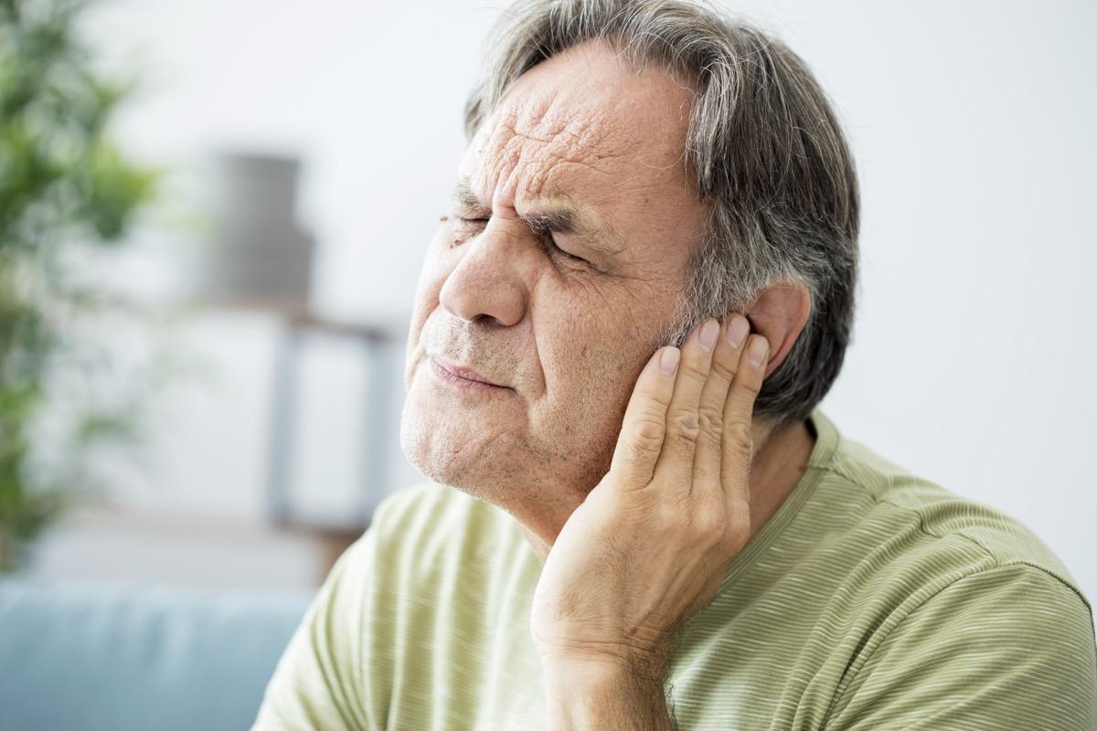 Senior white man holding his ear in pain