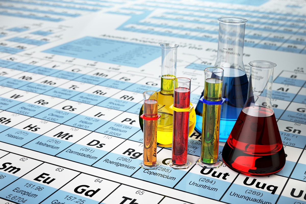 Science chemistry concept. Laboratory test tubes and flasks with colored liquids on the periodic table of elements, smarter facts
