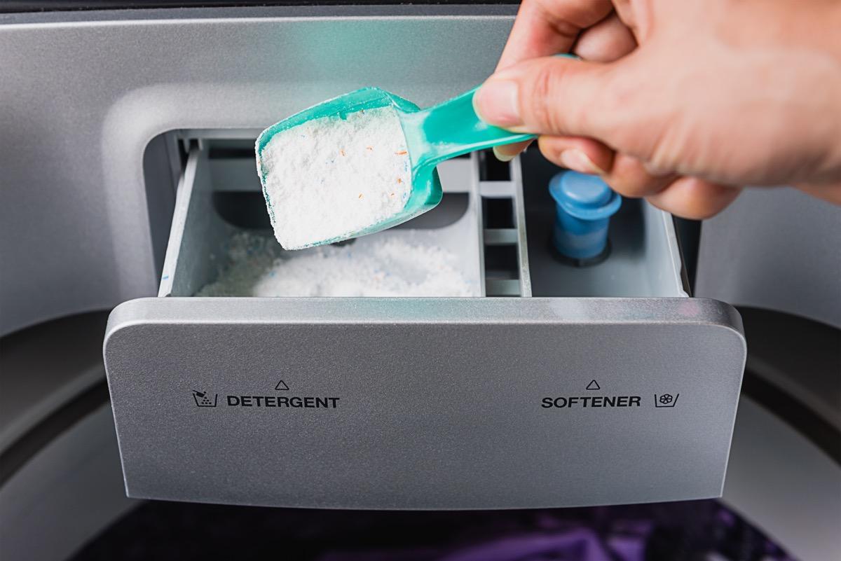 white hand putting powder detergent in washing machine
