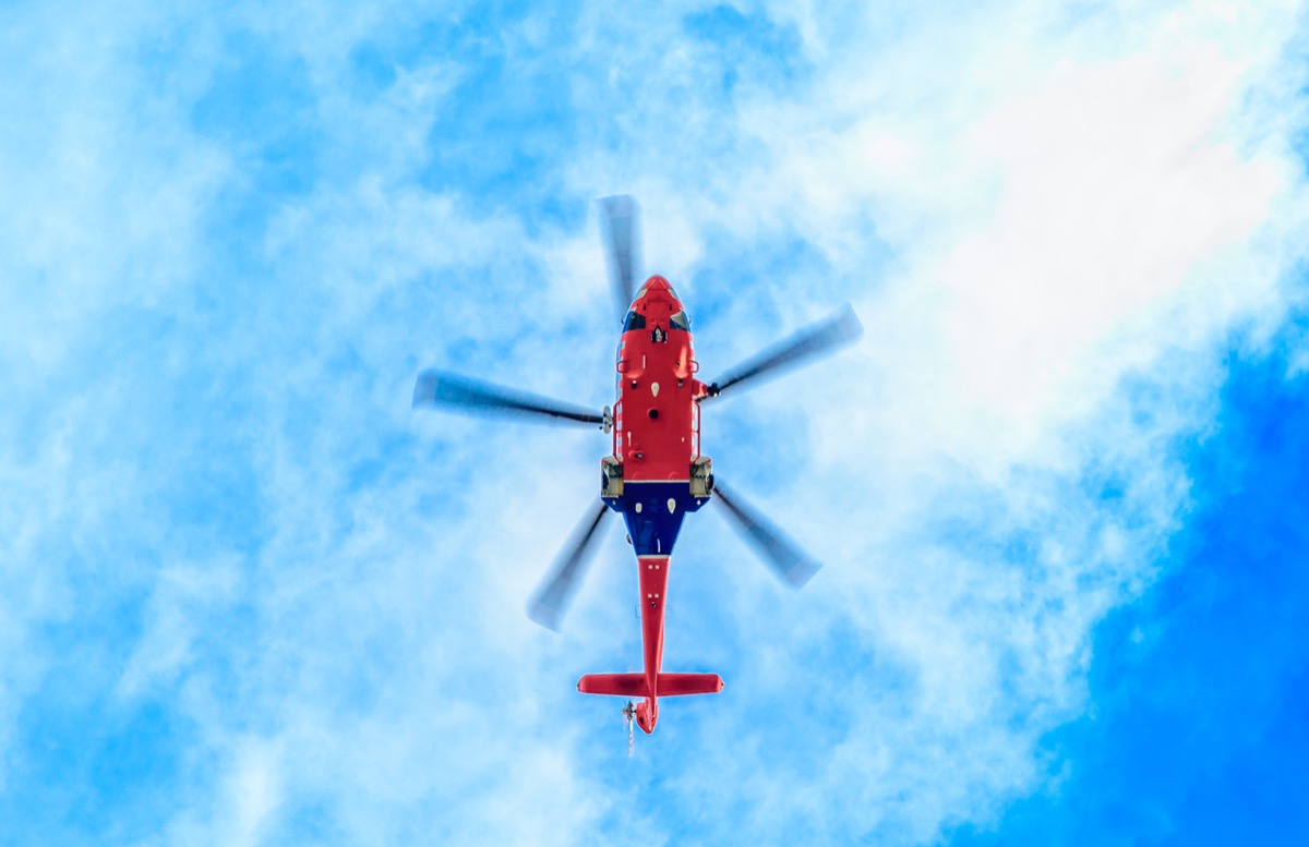 looking up underneath a blue and red helicopter against a blue sky with light clouds