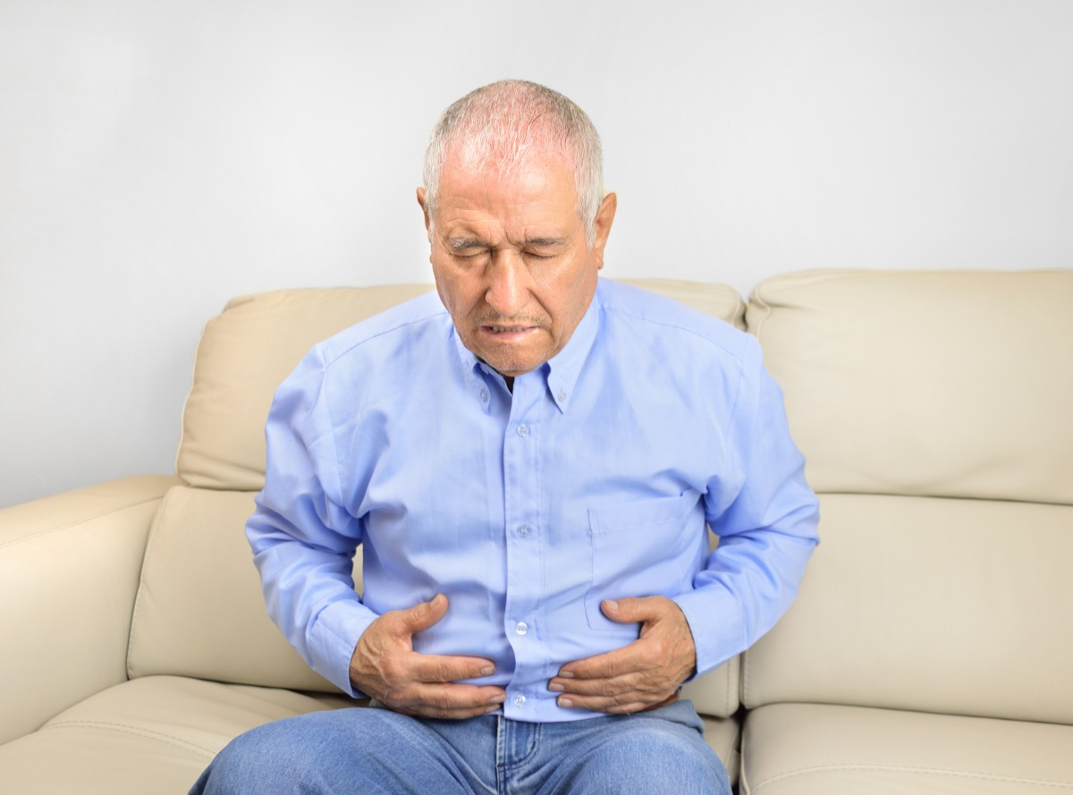 Senior man suffering stomach ache sitting on a couch in the living room at home