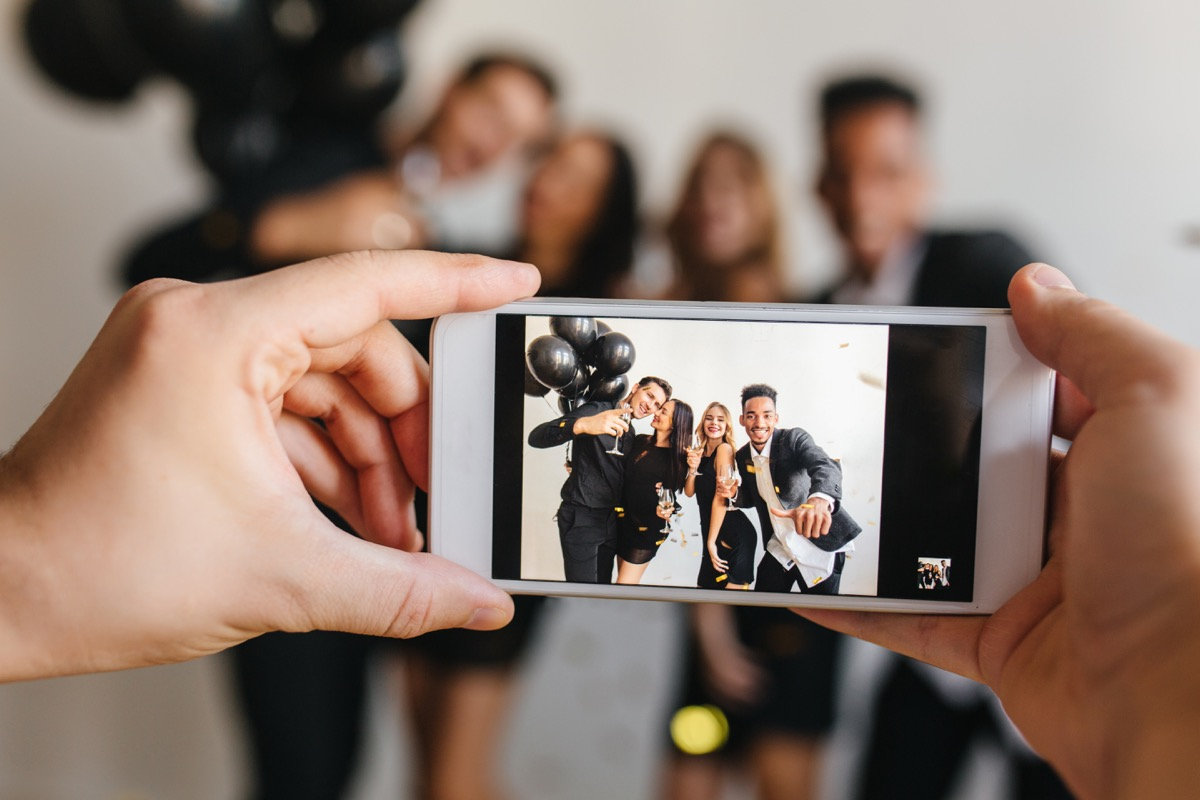 Blur portrait of blissful young people posing with balloons at birthday party with hands holding phone on foreground. Man taking photo of friends celebrating something and using smartpone. - Image