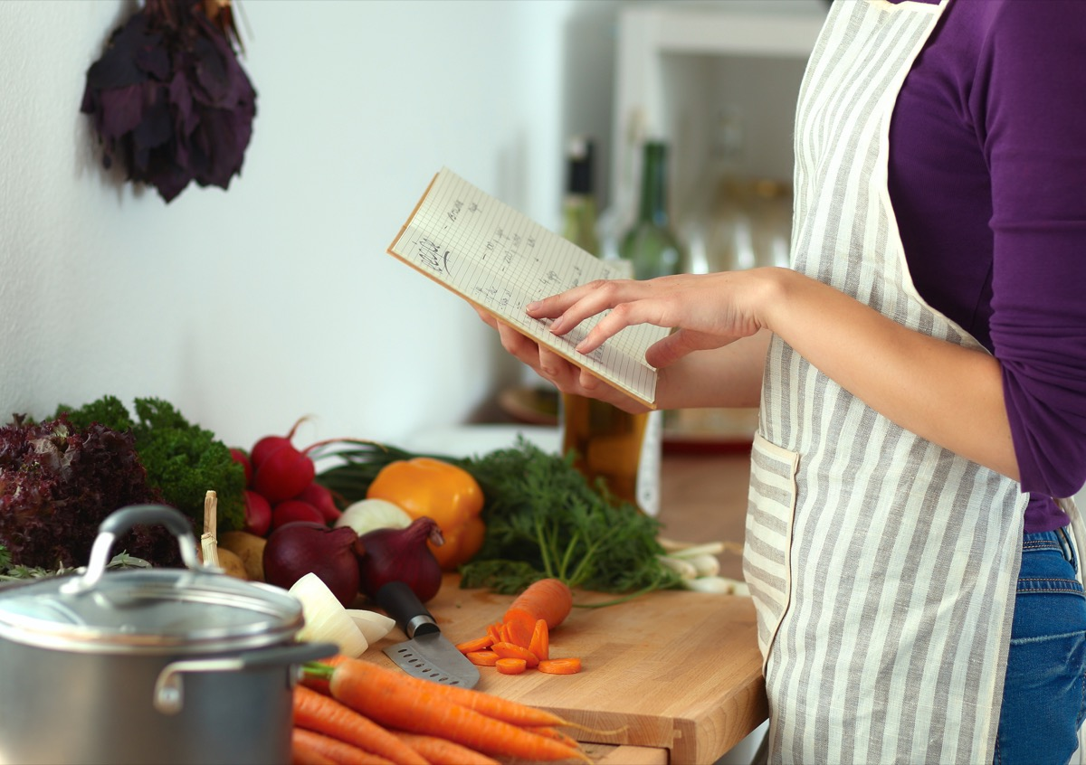 Woman Using a Cookbook in the Kitchen {Home Organization Tips}
