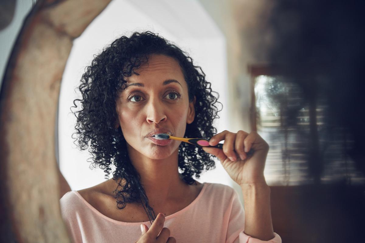 Woman looking in the mirror and brushing her teeth, ways you're damaging teeth