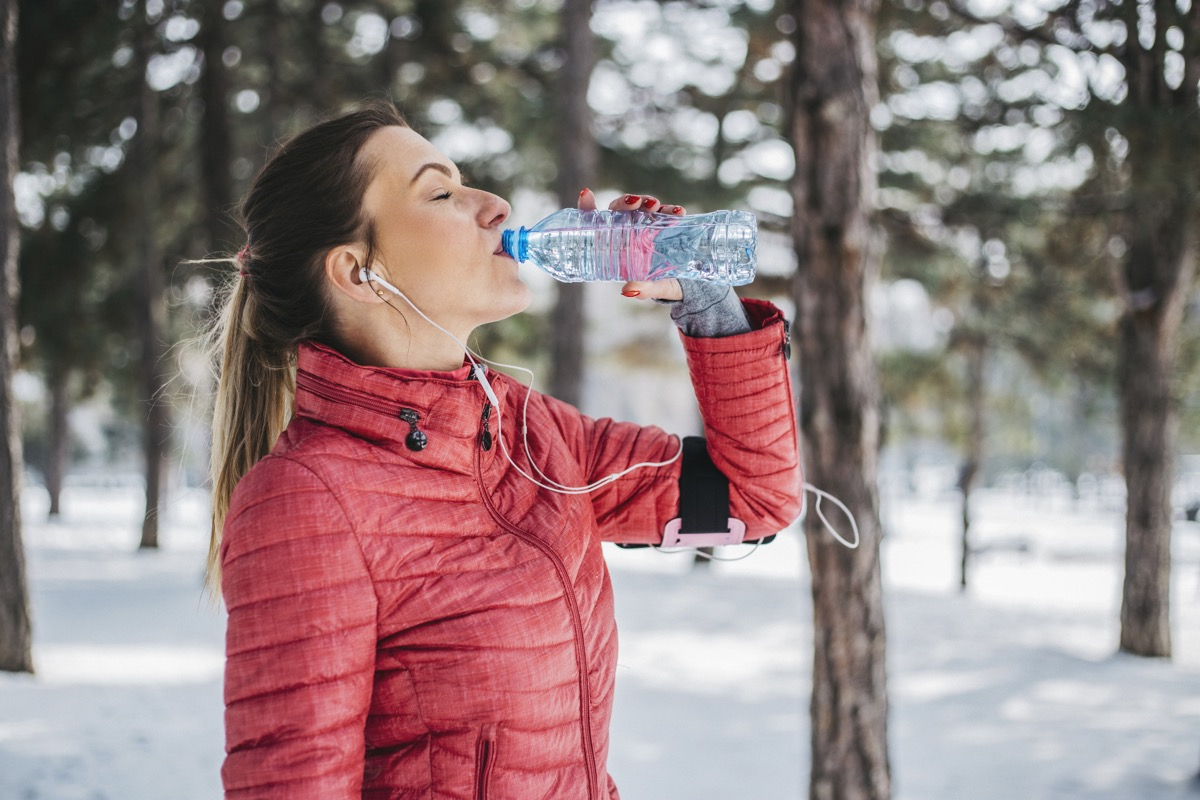 Woman drinking water outside in the winter after going for a jog