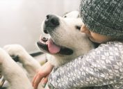 woman squeezing happy dog