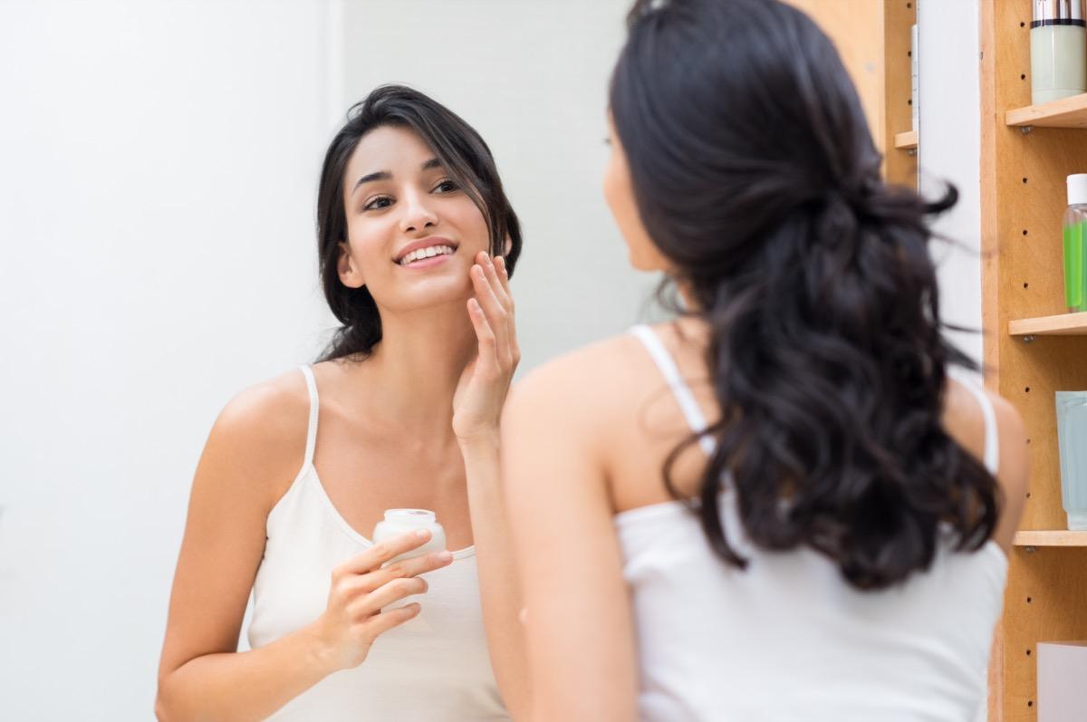 Woman moisturizing her face