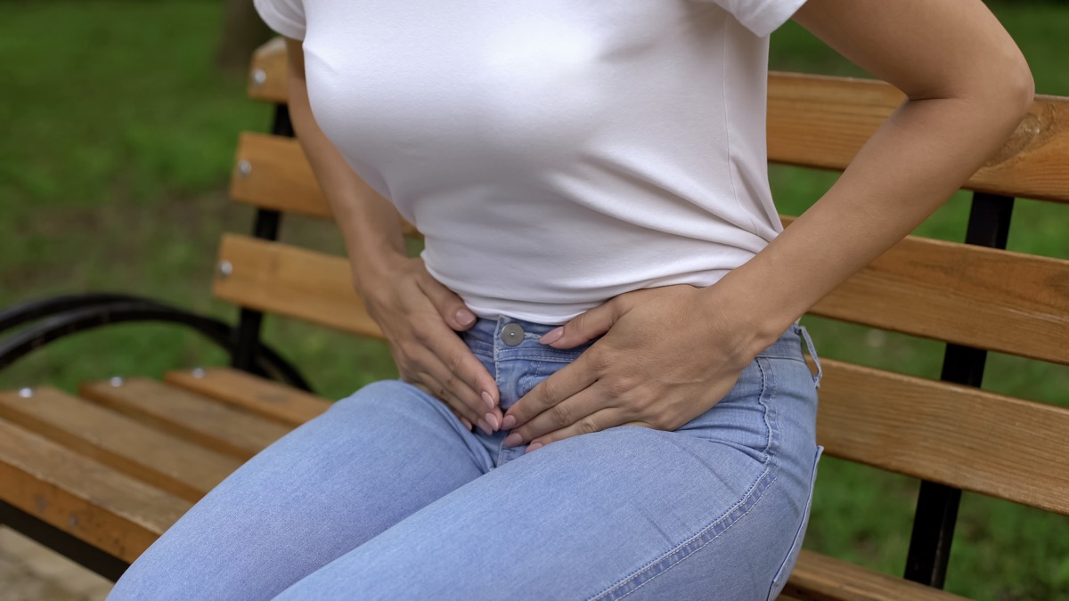Woman suffering from cystitis, touching abdomen and feeling pain, healthcare