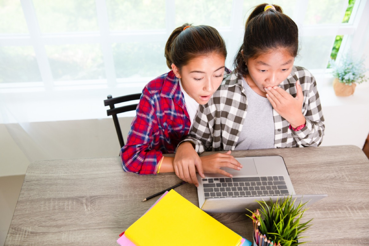 two young girls looking at laptop screen, parenting is harder