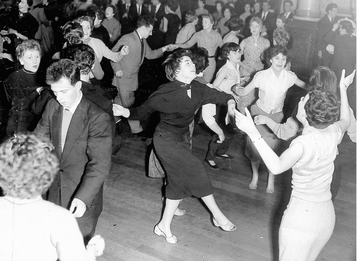 1950s young dancers crowd the floor for a rock n roll dance, cool grandparents