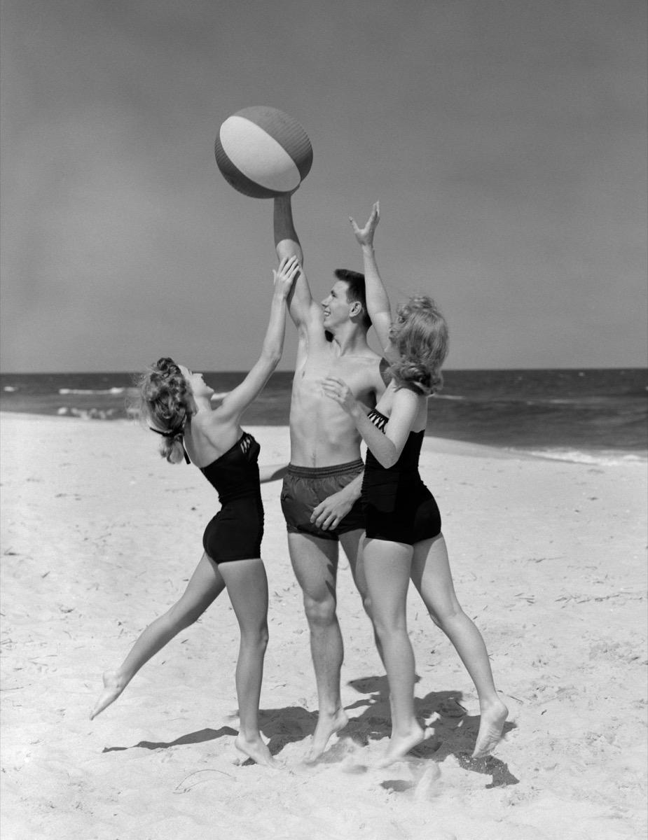 Two 1950s female teens reach for beach ball in male teens hands on beach, cool grandparents