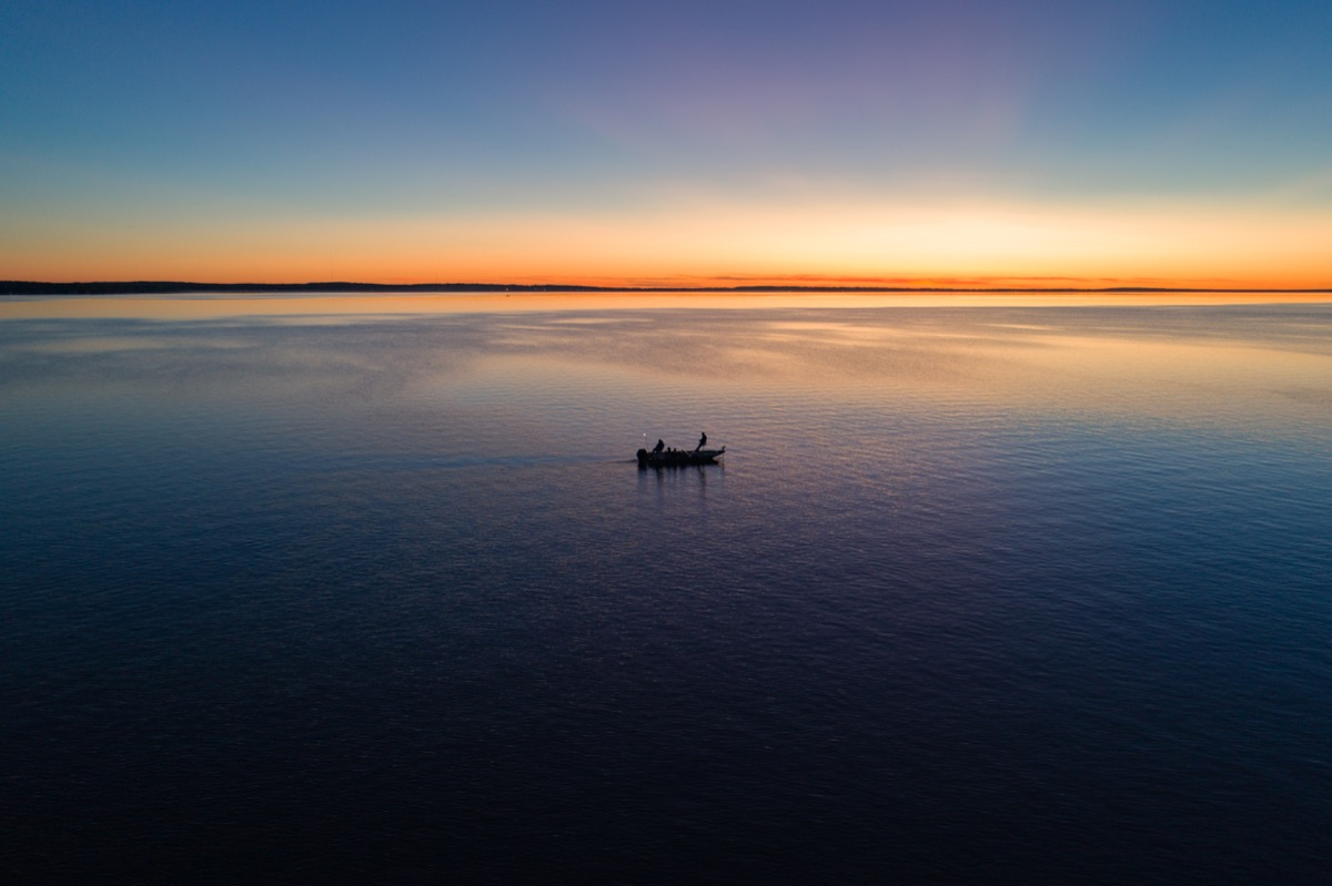 A small fishing boat on Houghton Lake at sunrise, state fact about michigan