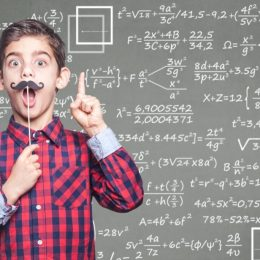 Little boy with fake mustache standing in front of chalkboard with math equations