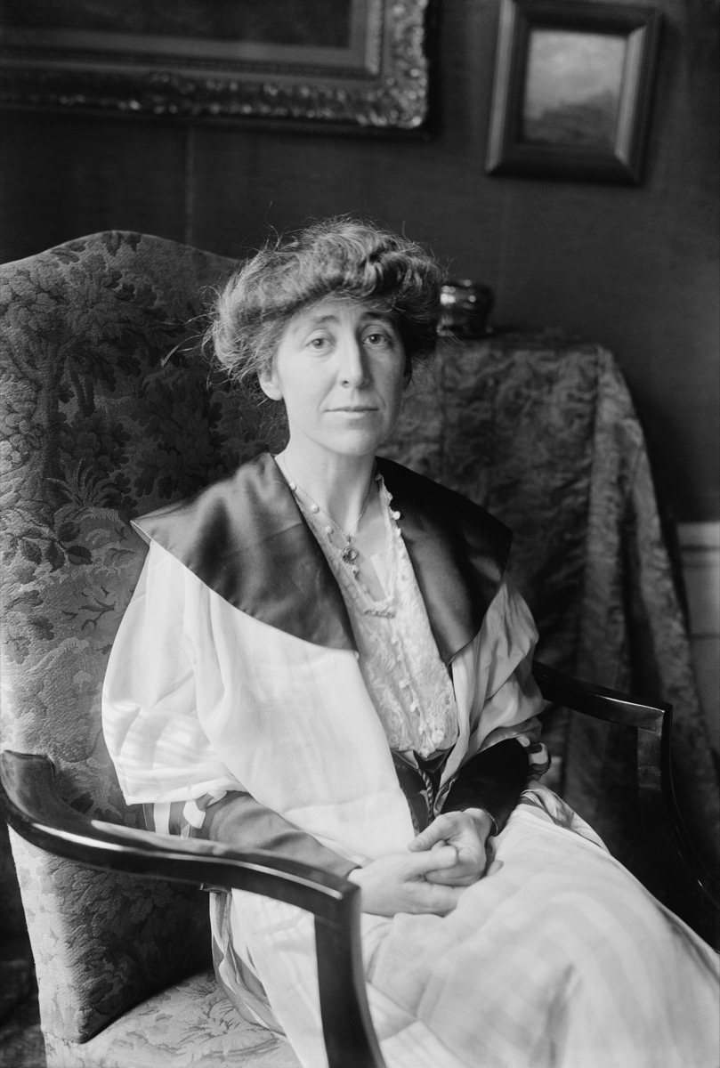 black and white photo of Jeannette Pickering Rankin sitting in a damask chair with wooden handles, state fact about Montana