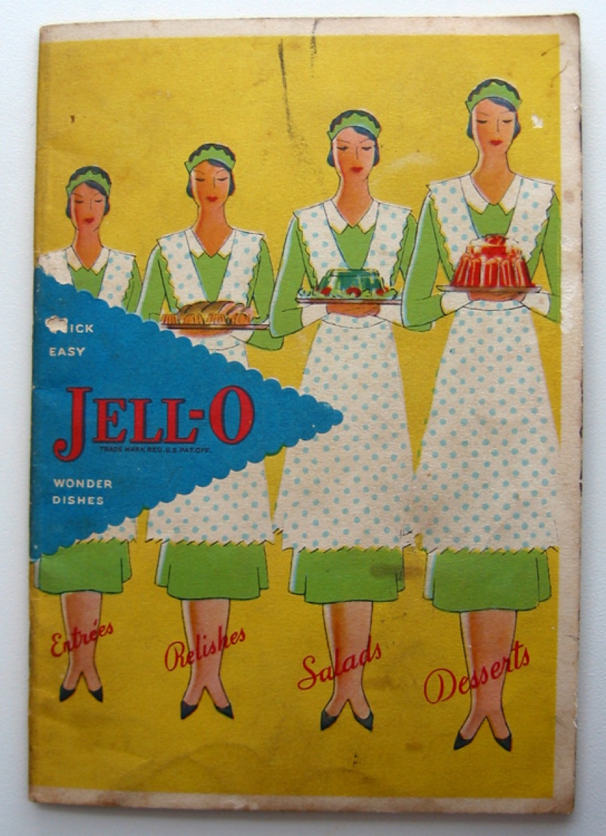 The front cover has a yellow background and a blue triangle behind the title. There are four maids dressed in green with green polka dot aprons, carrying a variety of Jell-O molds.