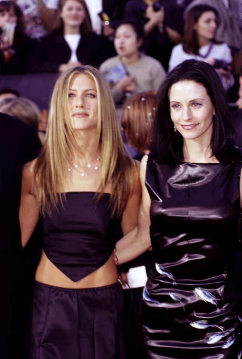 Celebrities Jennifer Aniston in black handkerchief top and Courteney Cox at 1999 Screen Actors Guild Awards