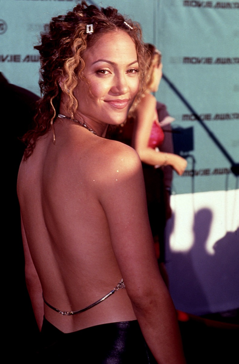 Celebrity Jennifer Lopez in backless dress with body glitter and barrettes at 1998 MTV Movie Awards