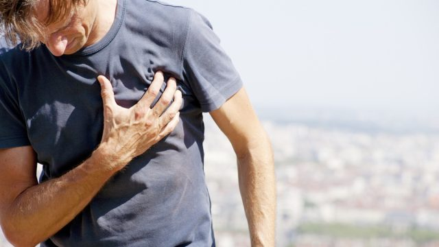 middle aged man holds heart while outside