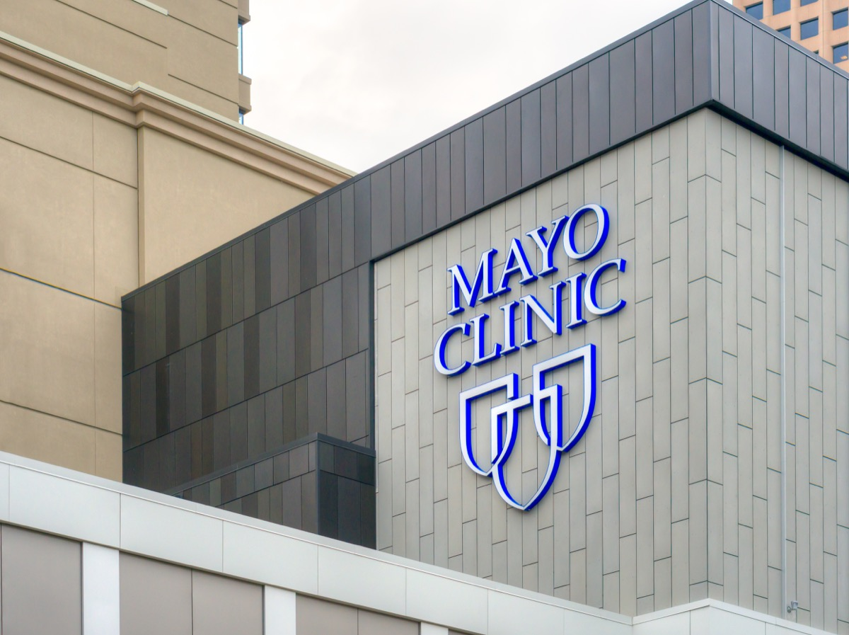 Mayo Clinic entrance and sign on side of white building, state fact about Minnesota