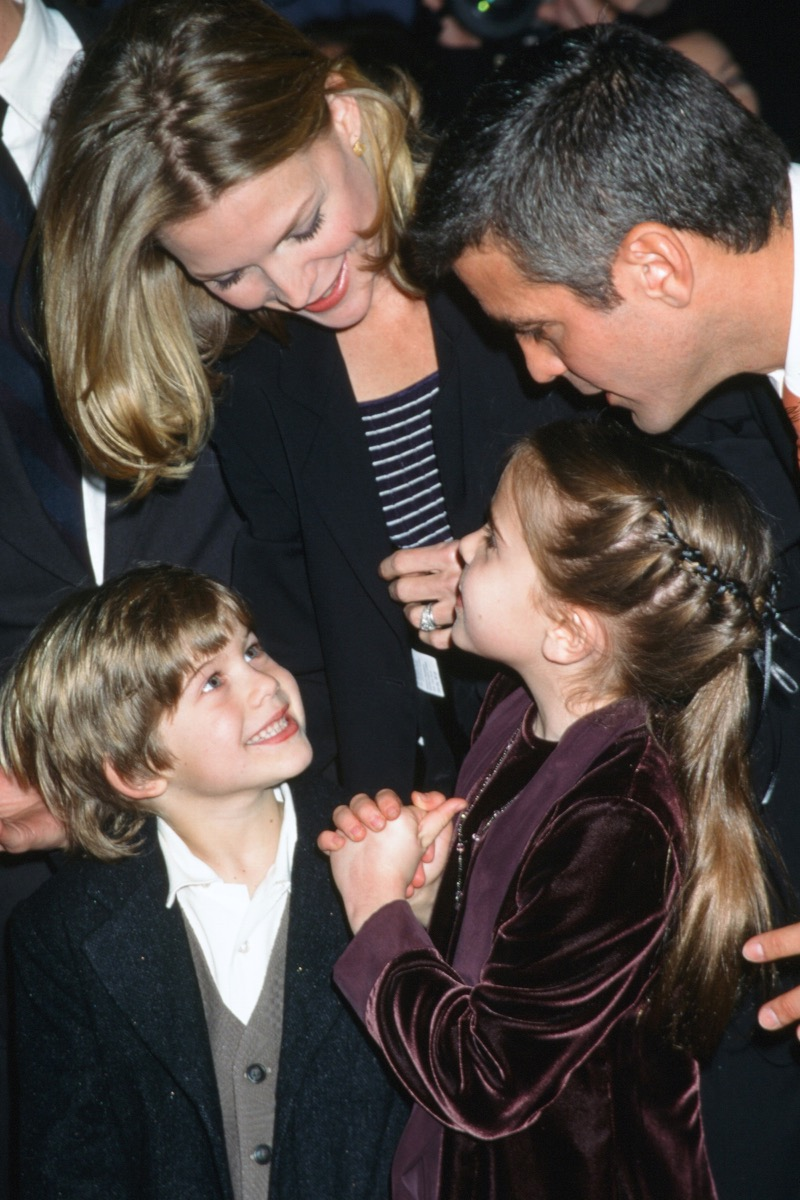 Celebrities Michelle Pfeiffer and George Clooney lean over their One Fine Day Costars Alex D Linz and Mae Whitman at 1996 premiere