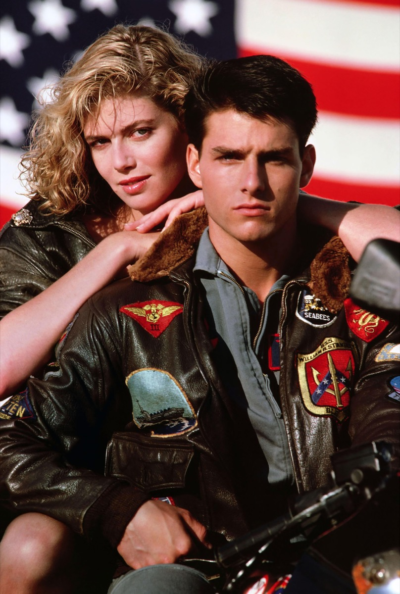 Tom Cruise in bomber jacket with Kelly McGillis leaning on his back in Top Gun movie, Cruise wears a '90s fashion trend