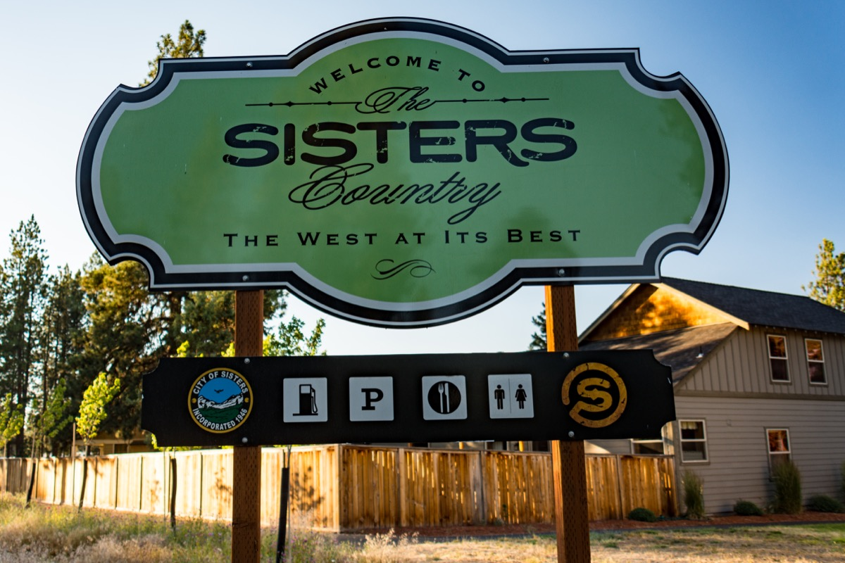 Welcome sign for the town of Sisters Oregon at dusk in the summer reads The West At Its Best, state fact about oregon