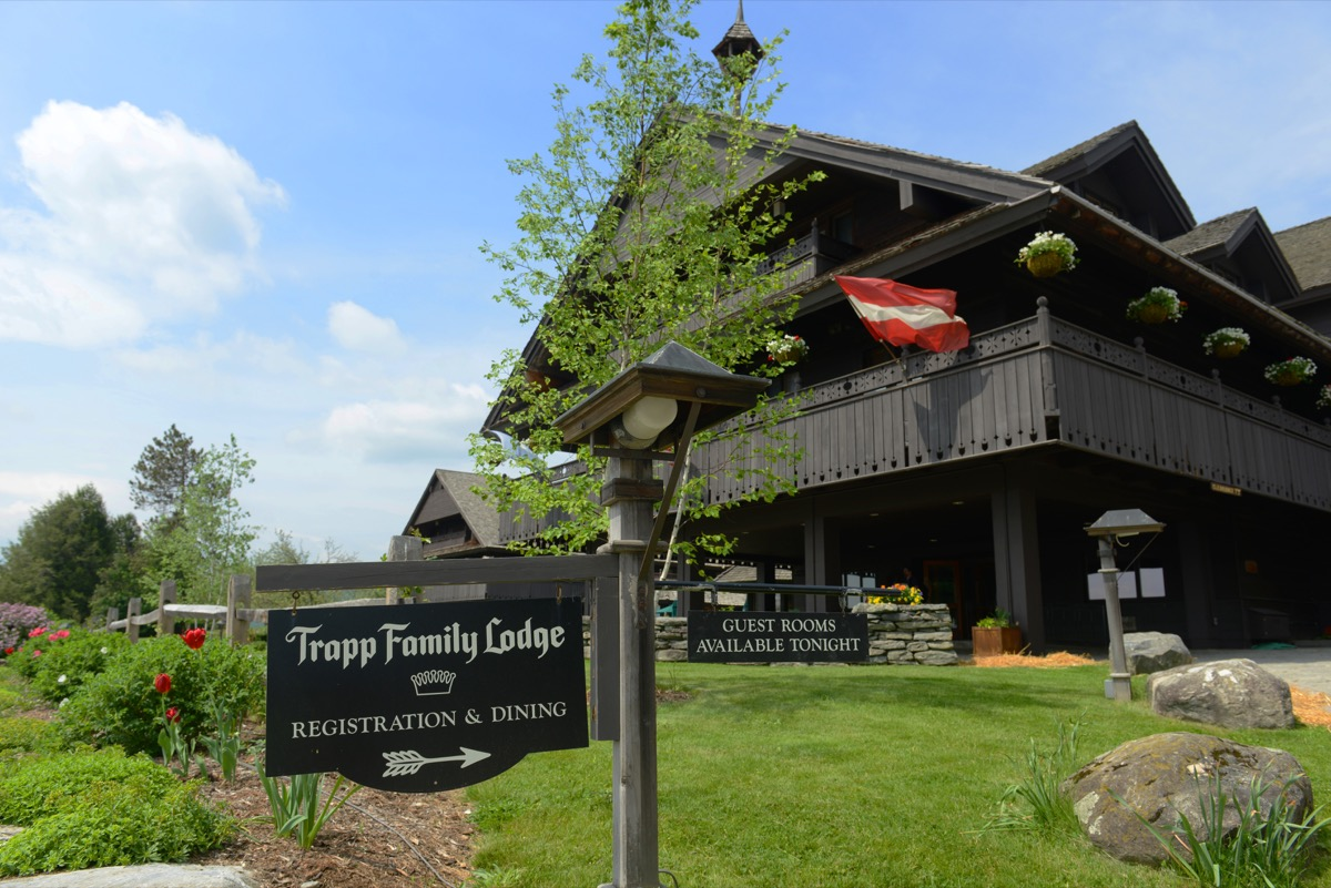 Trapp Family Lodge sits behind inn sign on a sunny day, state fact about vermont
