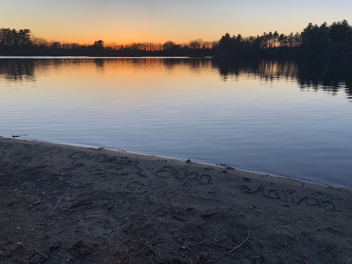 View from the shore of Lake as sun sets, state fact about massachusettes