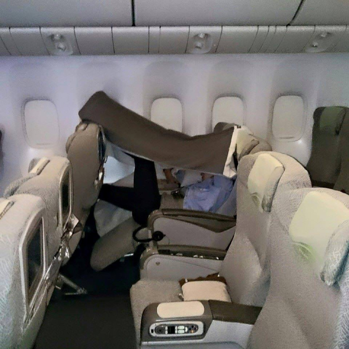 Airline passenger with blanket over head photos of terrible airplane passengers